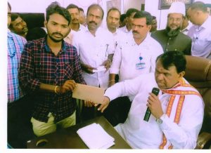 distributing the check to the beneficiary at the Grounding Mela.