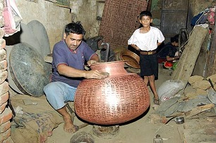 Thathera craftsman shaping a brass utensil at Jandiala