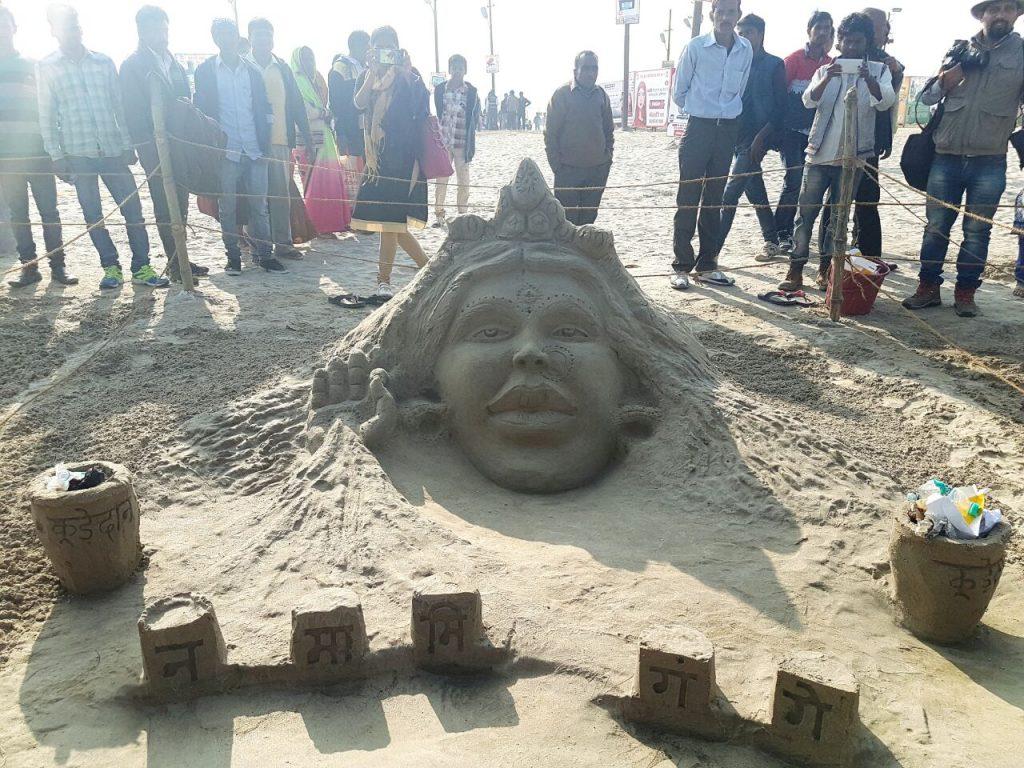 नमामी गांगे हेतु गंगा के तट पर रेत से कलाकृति