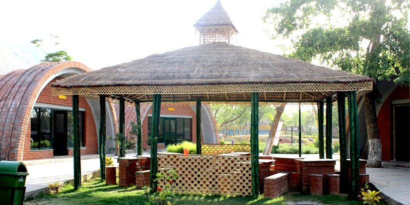 A closer view of the hut-shaped shades above the seating arrangements in the park.