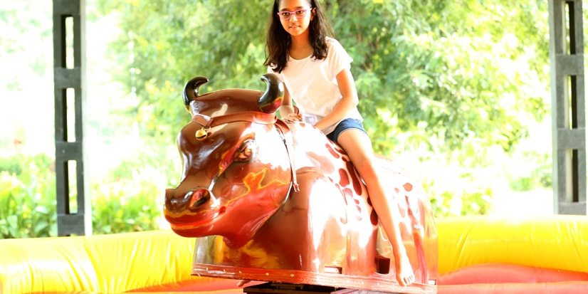 A little girl taking the artificial bull ride.