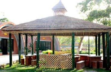 A closer view of the hut-shaped shades above the seating arrangements in the park