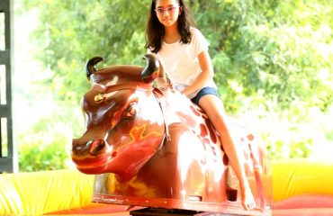 A little girl taking the artificial bull ride