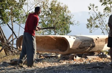 A tribesman making a log drum